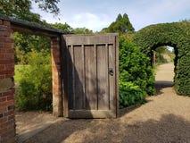 Trädgård med dörröppningen och den välvda busken royaltyfri fotografi
