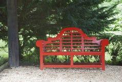 Trädgård med den röda orientaliska stilbänken under ett träd Fotografering för Bildbyråer