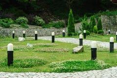 Trädgård med gräs, buskar och lampor arkivbilder