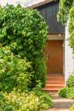 Trädgård med nya röda hallon som är klara för skörd och en sikt till en husdörr på den tyska byn Fotografering för Bildbyråer