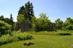 Trädgård och staket på en sommardag Arkivfoto