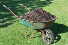 Trädgård-skottkärra som fylls med jord på en lantgård Arkivfoto