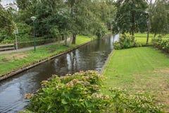 Trädgårdar och en idyllisk kanal royaltyfria foton