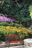 Trädgårdbänken i parkerar färgrik bildbakgrund för blomman royaltyfri fotografi