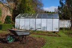 Trädgård med skottkärran och växthuset Royaltyfri Bild