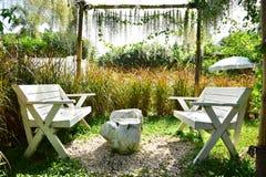 Trädgården och de vita stolarna royaltyfria foton