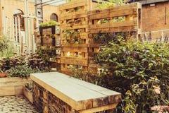Trädgårdhörn i industriell stad Liten växtskärm Bruk av utrymme TräEco stil Yttre designbegrepp Tappningtoning arkivbild