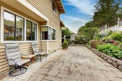 Trädgårdområde med stentegelplattagolvet och härlig rabatt Royaltyfri Fotografi