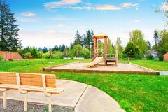 Trädgårdområde med trälekuppsättningen för ungar med gungor och glidbanor Arkivfoto