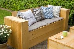 Trädgårds- bänk i trädgård Arkivfoto