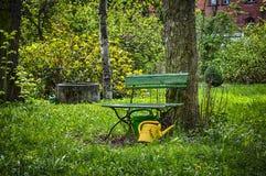 Trädgårds- bänk med den gula vattenkannan Royaltyfri Bild