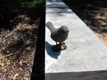 Trädgårds- bänk med den keramiska fågeln arkivbilder