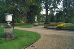 Trädgårds- bana med en prydnad och en romarestaty på en sockel royaltyfria bilder