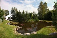 Trädgårds- damm framme av huset Damm i en gård av en stor stuga Royaltyfri Bild