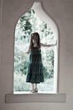 trädgårds- flicka som ut ser det gammala slottfönstret royaltyfria foton