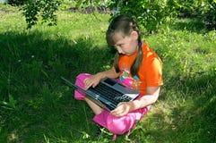 trädgårds- flickabärbar dator arkivbilder