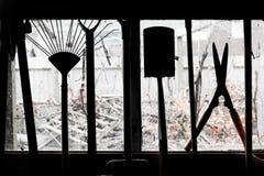 Trädgårds- hjälpmedel som hänger i ett skjulfönster fotografering för bildbyråer