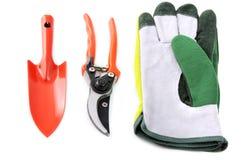 Trädgårds- hjälpmedel som skyffeln, handskar, sax på vit isolerade backgr Arkivbild