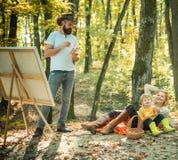 Trädgårds- parti för höst - fader, mather och son Campa med ungar Tycka om bra väder Höst för mankonstnärmålning royaltyfria foton