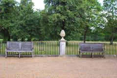 Trädgårds- prydnad på en sockel och träbänkar, plats arkivbild