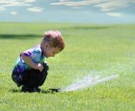 trädgårds- sprinkler för pojke Arkivbild