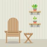 Trädgårds- stol och tabell med krukväxter på träväggen Royaltyfri Fotografi