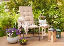 Trädgårds- stol och tabellen på terrass blommar busken Royaltyfri Bild