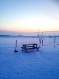 Trädgårds- tabell i snöig solnedgång i Sverige Royaltyfri Fotografi