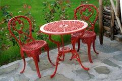 Trädgårds- tabell som är röd med att matcha stolar Royaltyfri Fotografi