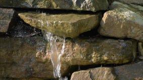 Trädgårds- vattenfall av stenar vatten flödar till och med stenen Morgonsolskenen på vattenfallet lager videofilmer