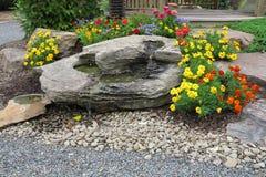 Trädgårds- vattenfall och blommor Fotografering för Bildbyråer