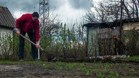 Trädgårdsmästare Digs för ung man jordningen med en skyffel i trädgården Tid schackningsperiod stock video