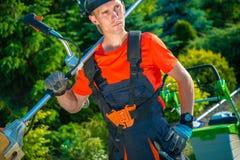 Trädgårdsmästare med skuldragräsklippningsmaskinen royaltyfri fotografi