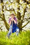 Trädgårdsmästare sitter spaden som bevattnar kan trädet Royaltyfria Bilder