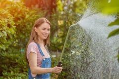 Trädgårdsmästare som bevattnar växter Arkivbilder