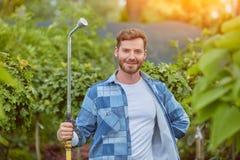 Trädgårdsmästare som bevattnar växter Arkivbild