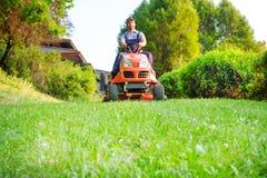 Trädgårdsmästare som kör en ridninggräsklippare i trädgård arkivbilder