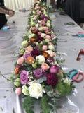 Trädgårdsmästare som ordnar blommor på den äta middag tabellen royaltyfria bilder