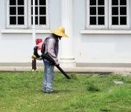 Trädgårdsmästare Using Leaf Blower på nytt klippt gräsmatta Arkivfoton