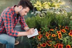 Trädgårdsmästaredanandeanmärkningar i anteckningsbok, medan kontrollera växter i trädgård Arkivfoto