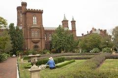 Trädgårdsmästaren arbetar framme av en slott royaltyfri foto