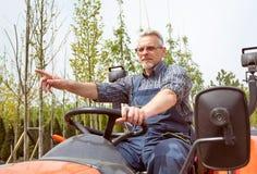 Trädgårdsmästareritter på traktoren på trädgårdlagret arkivfoton