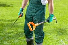 Trädgårdsmästares händer med trädgårds- hjälpmedel Arkivbild