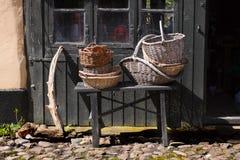 Trädgårdsmästaretappningkorgar på ett romantiskt gammalt lantligt lantgårdhus - retro stilleben Arkivfoton