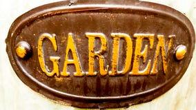 Trädgårdtecken - brunt ovalt med gula bokstäver royaltyfri bild