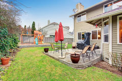 Trädgårduteplatsområde med tabelluppsättningen och det stängda röda paraplyet Fotografering för Bildbyråer
