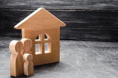 Trädiagram av familjen står nära ett trähus Begreppet av att finna ett nytt hem som flyttar sig En sund stark familj arkivbilder