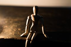 Trädocka på en svart bakgrund i ljuset av en stearinljus i en krus royaltyfri foto