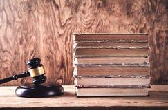 Trädomareauktionsklubba och böcker på träskrivbordet Lag och rättvisa arkivfoto
