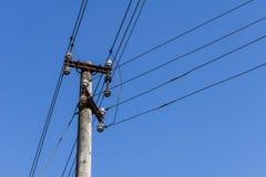 Träelektrisk pol med trådar i den blåa himlen i bakgrunden Arkivfoto